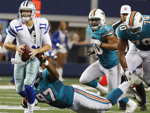 Dallas Cowboys quarterback Rudy Carpenter (11) is tackled by Miami Dolphins defensive tackle Kheeston Randall (97) during the second half of a preseason NFL football game