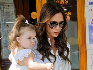 Victoria Beckham holding Harper Beckham in her arms leaving Pastis