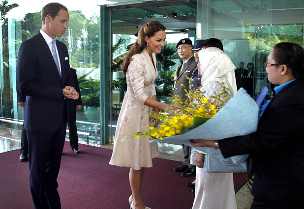 Prince William, the Duke of Cambridge, left, watches his wife Kate, the Duchess of Cambridge, center, receives flowers upon arrival at the VIP terminal of Changi International Airport on Tuesday, Sept. 11, 2012 in Singapore. The British royal couple is on an official three-day trip to Singapore. (AP Photo/Wong Maye-E, Pool)