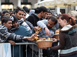 Lucky customers are given snacks as they wait in line outside the Apple Store in Covent Garden