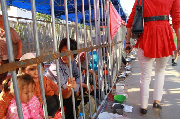 Beggars caged behind bars at temple fair to prevent harassment of tourists, Nanchang, Jiangxi Province, China -