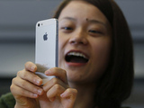 A customer gets to grips with her white iPhone 5 in Hong Kong.