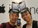 Customers wearing iPhone hats try out their new toys in the Apple store, Tokyo