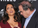Oliver Stone adjusts Salma Hayek's cleavage at Savages photocall in London.