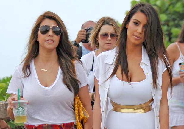 Kim Kardashian seen with sister Kourtney Kardashian at the beach wearing a white swimsuit and long cover-up  while filming the upcoming season of &#39;Kourtney & Kim Take Miami&#39;.