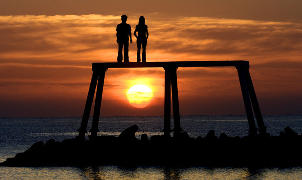 The sun rises over the giant sculpture by Sean Henry of a man and woman situated 300 yards out to sea off the coast of Northumberland at Newbiggin-by-the-Sea.