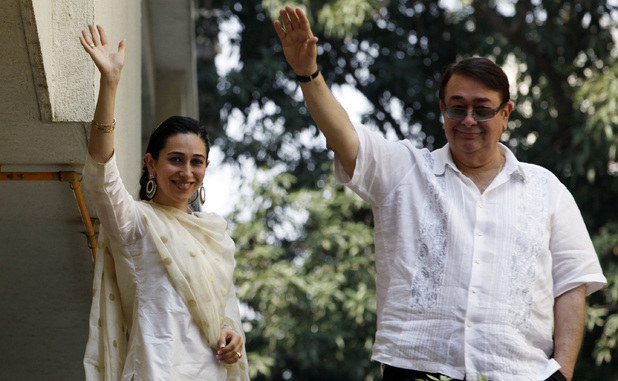 Randhir Kapoor, right, and Karisma Kapoor, father and sister respectively of Kareena Kapoor, wave from a balcony after the wedding of Saif Ali Khan and Kareena Kapoor in Mumbai