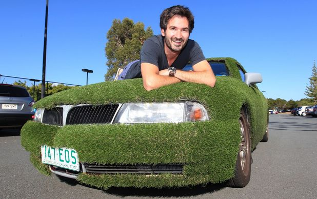 The ultimate green car: Tim poses with his astro turf covered 1998 Mitsubishi Magna car