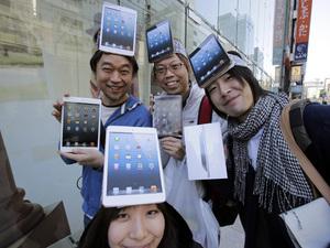 Customers Kazuki Miura, left, Mio Kawai, bottom, Hisanori Kogure, center, and Kota Suzuki show off Apple's iPad Mini after they bought at a store in Tokyo