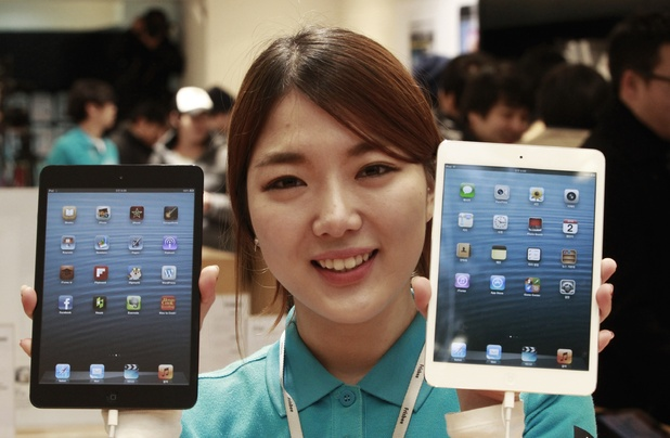 A salesclerk poses with new iPad Minis for the media at an Apple store in Seoul, South Korea