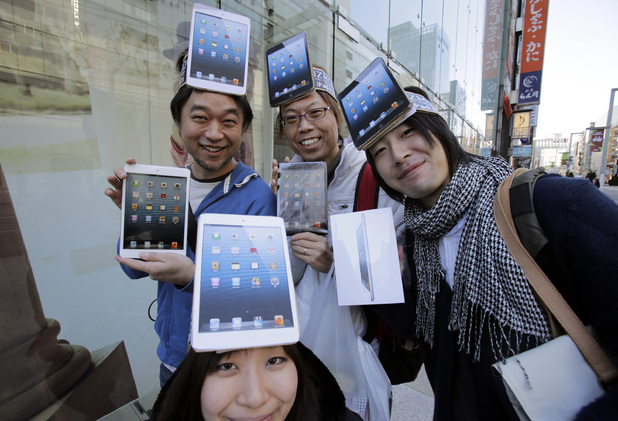 Customers Kazuki Miura, left, Mio Kawai, bottom, Hisanori Kogure, center, and Kota Suzuki show off Apple's iPad Mini after they bought at a store in Tokyo