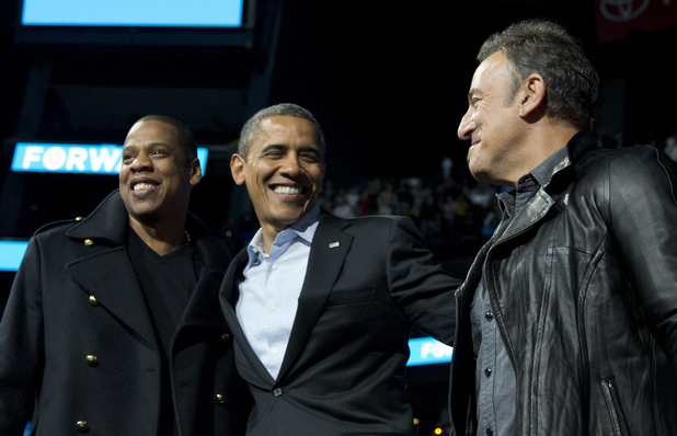 President Barack Obama is flanked on stage by musicians Jay-Z, left, and Bruce Springsteen at a campaign event at Nationwide Arena