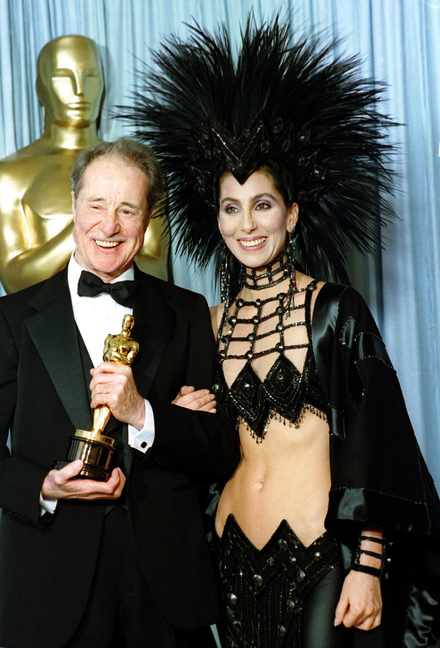 Cher, Bob mackie as she poses with actor Don Ameche after presenting him with the Oscar for best supporting actor