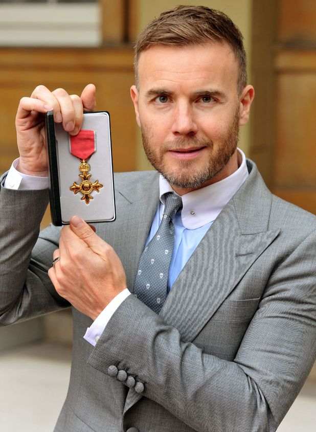 Gary Barlow holds his OBE, for services to the entertainment industry and to charity, which was awarded to him by Queen Elizabeth II during an Investiture ceremony at Buckingham Palace in central London.