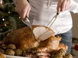 Woman carving Christmas dinner turkey