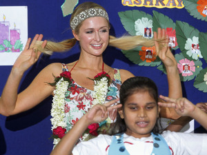 Paris Hilton, left, dances with children during her visit at Ashray, an orphanage in Mumbai, India, Monday, Dec. 3, 2012