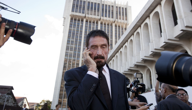 Software company founder John McAfee talks on his mobile phone after a press conference outside the Supreme Court in Guatemala City, Tuesday, Dec. 4, 2012.