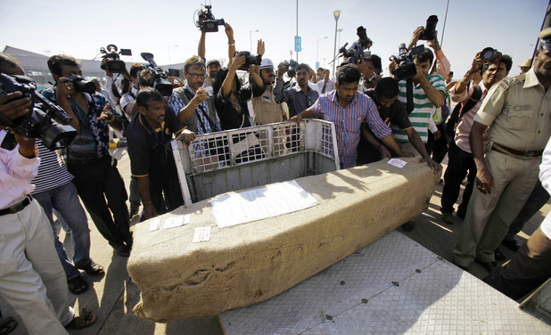Indian journalists take pictures of a casket containing the body of Jacintha Saldanha following its arrival in Mangalore, India