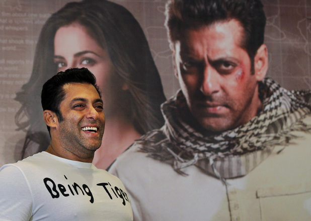Salman Khan smiles as he stands in front of a poster showing himself and actress Katrina Kaif at a press conference to promote the film 'Ek Tha Tiger' or 'Once There was a Tiger', in New Delhi, India, Sunday, August 12, 2012.