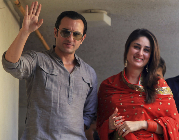 Saif Ali Khan and Kareena Kapoor step out on a balcony to greet waiting fans after getting married in Mumbai in 2012.
