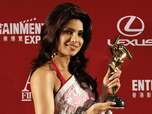 "India actress Priyanka Chopra celebrates with the trophy after winning the Nielsen Box Office Award for her role in ""Service"" at the Asian Film Awards in Hong Kong Monday, March 23, 2009."