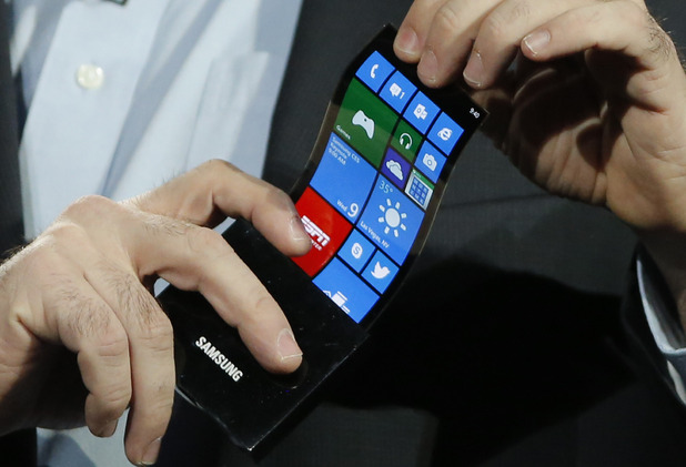 Eric Rudder, chief technical strategy officer of Microsoft, holds a prototype Windows smartphone with a flexible OLED display during Samsung's keynote address at CES 2013