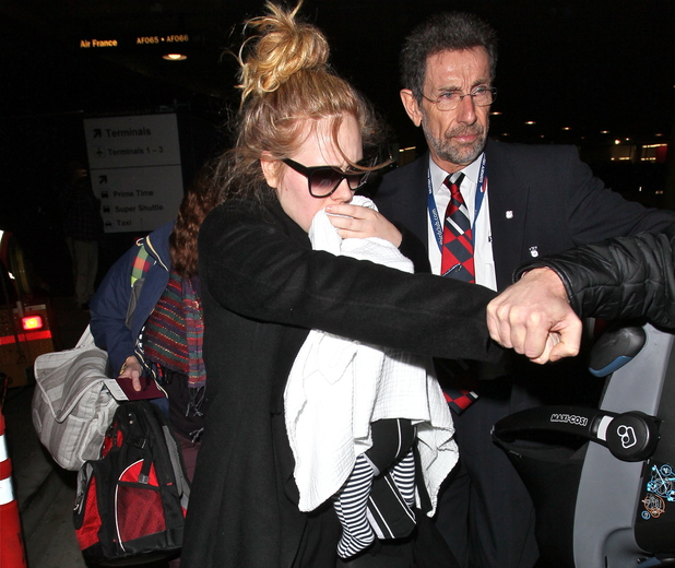 Adele arrives into Los Angeles International Airport (LAX) amid tight security. Her baby son is hidden from view under a blanket.