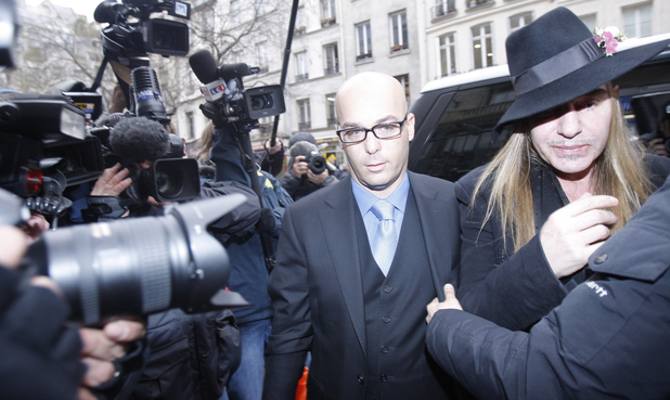 John Galliano, right, arrives at a police station in Paris, Monday, Feb. 28, 2011. Galliano arrived Monday at a Paris police station to face accusations that he made illegal anti-Semitic slurs