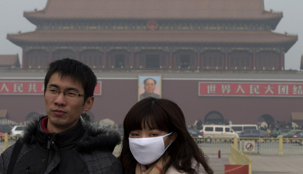 A woman wears a mask as she visits Tiananmen Square in Beijing