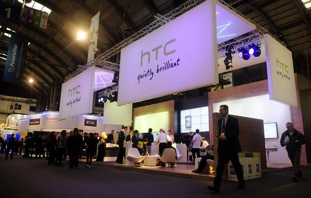 Participants gather around the HTC stand at the Mobile World Congress in Barcelona, Spain, Thursday, Feb. 17, 2011. The Mobile World Congress is held from Feb. 14-17