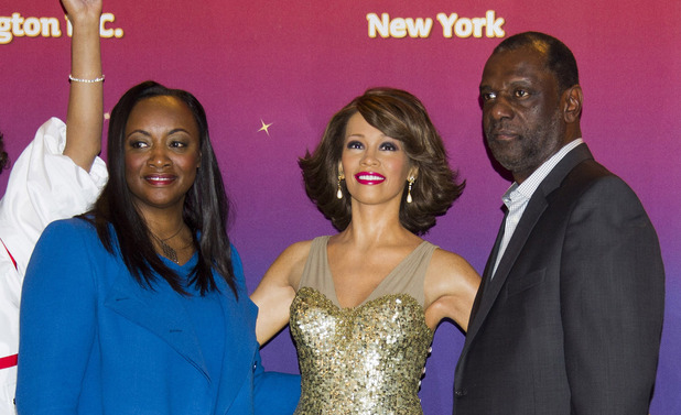 Pat and Gary Houston pose with four wax figures of Whitney Houston, immortalizing memorable moments in her career at Madame Tussauds