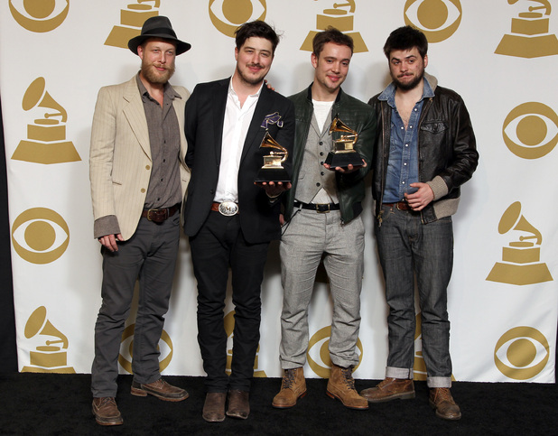 Ted Dwane, Marcus Mumford, Ben Lovett and Winston Marshall of the band Mumford & Sons pose backstage with the best long form music video award for 'Big Easy Express' and the album of the year award for 'Babel' at the 55th Annual Grammy Awards