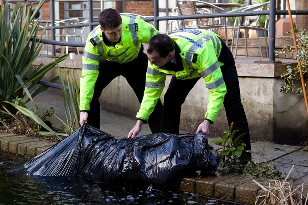 A body bag is pulled from the water