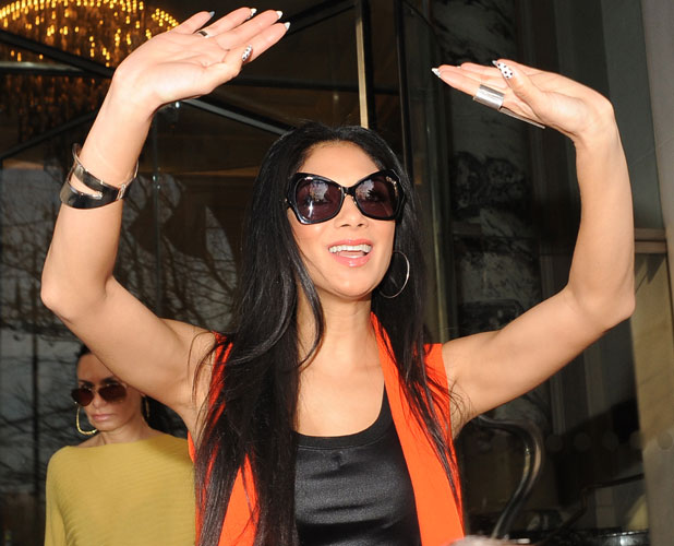 Nicole Scherzinger in an orange vest outside her London hotel on 4 March 2013