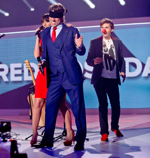 David Tennant prepares to kiss an unknowing John Bishop, who is actually expecting a peck from Davina McCall
