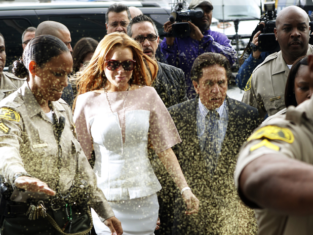 Lindsay Lohan is showered with gold glitter on her way into a Los Angeles courtroom - March 18, 2013