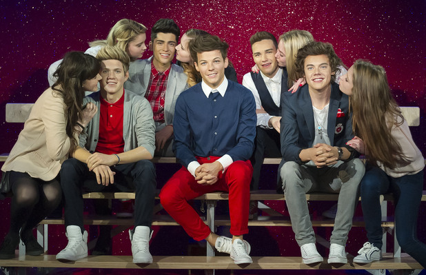 One Direction's waxworks surrounded by fans at Madame Tussauds.