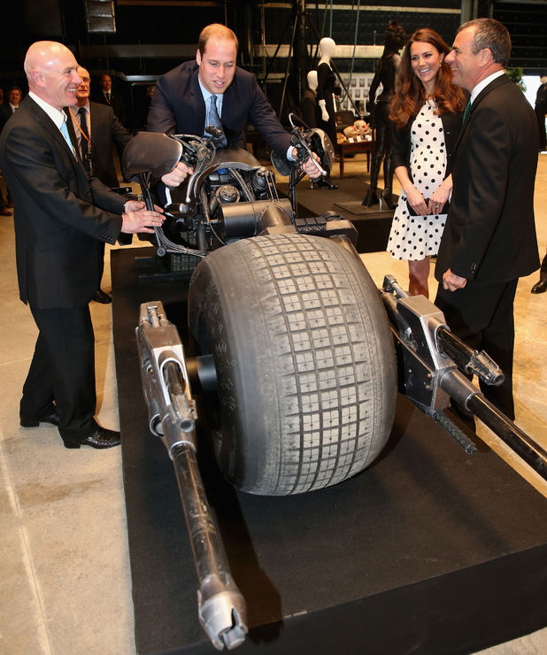 The Duchess of Cambridge watches as Duke of Cambridge sits on the 'Batpod' during their visit to Warner Bros studios in Leavesden.
