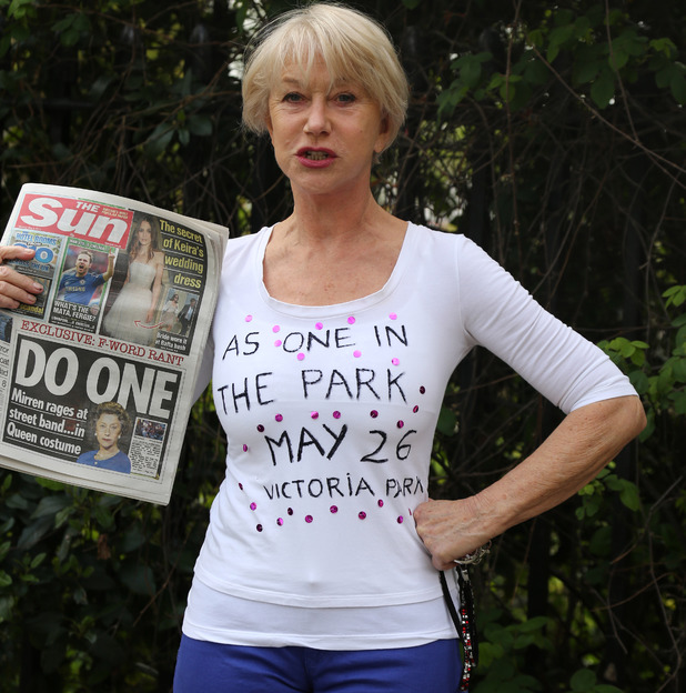 Helen Mirren holds up a tabloid headline about her drum outburst