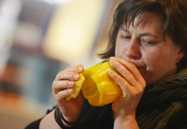 A member of the Vienna Vegetable Orchestra plays a yellow bell pepper in San Miguel market, Madrid, Spain