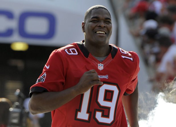 Former Tampa Bay Buccaneers player Keyshawn Johnson runs onto the field during halftime of an NFL football game as the Buccaneers honor their 2002 Super Bowl winning team Sunday, Dec. 9, 2012, in Tampa, Fla