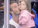 Recently-retired footballer cuddles up to Harper on a family trip to a hockey game.