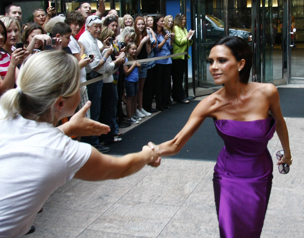 Victoria Beckham greets fans as she arrives at a hotel in Denver, Colo., on Friday, Aug. 7, 2009, for a guest judging appearance on a call back audition for the American Idol show.
