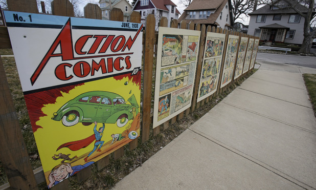 Superman comic book pages displayed on a fence outside of what was once Joe Shuster's boyhood home in Cleveland