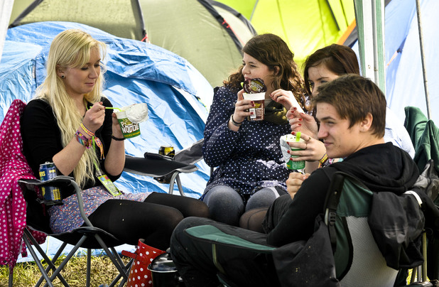 Revellers eat pot noddles outside their tents after arriving at the Glastonbury Festival 2011
