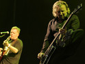 New Order's bass player Peter Hook, right, kicks out as singer Bernard Sumner takes to the micophone as the band play the Pyramid stage at the Glastonbury music festival, Glastonbury, England, Saturday June 25, 2005.
