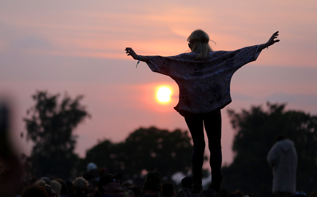 A woman stands on a rock at the stone circle as people gather for sunset at the Glastonbury Festival of Contemporary Performing Arts site at Worthy Farm, Pilton on June 26,