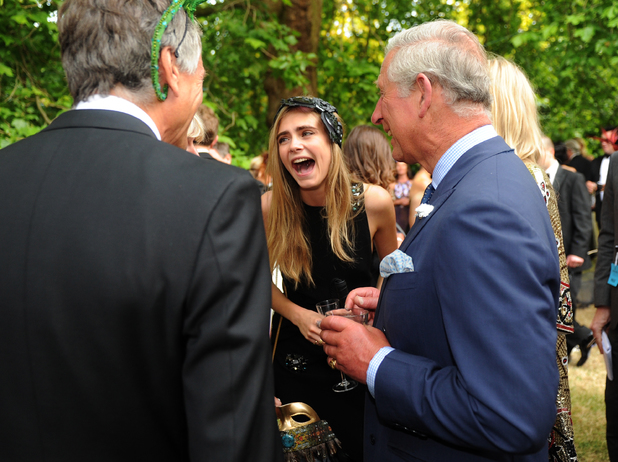 Cara Delevingne (2nd L) shows off a tattoo as she meets with Prince Charles, Prince of Wales as she and Poppy Delevigne (R) attend a reception hosted by The Prince of Wales and Duchess of Cornwall, a charity working to save the Asian Elephant from extinction in the wild, at Clarence House on July 09, 2013 in London, England