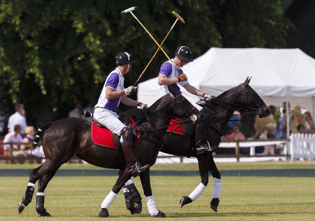 The Duke of Cambridge (left) and Prince Harry in action during The Jerudong Trophy at Cirencester Park Polo Club in Cirencester, Gloucestershire