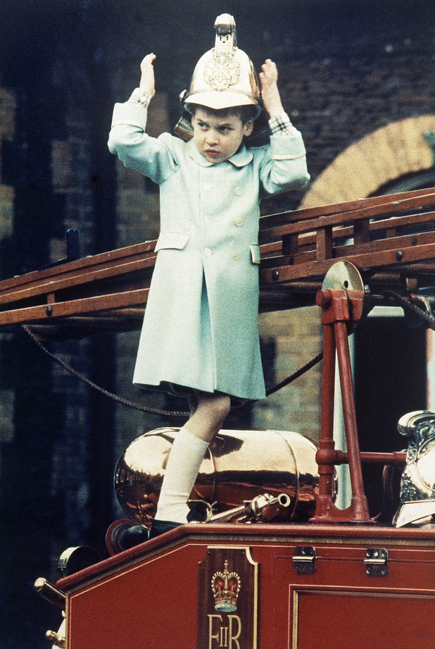 "Prince William aged 5, tries a fireman''s helmet on a vintage ""Merryweather fire engine at Sandringham House, Norfolk, England on Jan. 3, 1988 during the royal family's holiday on their Norfolk estate."